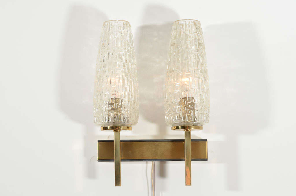 Brass two-arm wall sconce with cut glass shades.  France, circa 1960.  Beautifully made of solid brass with black edging, complemented by substantial glass sconces.  Item may be viewed at the 1stdibs@NYDC showroom at the New York Design Center,
