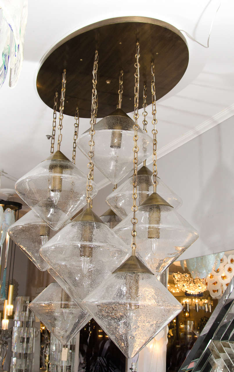 Custom prism globe chandelier with brass finish plate and chains.