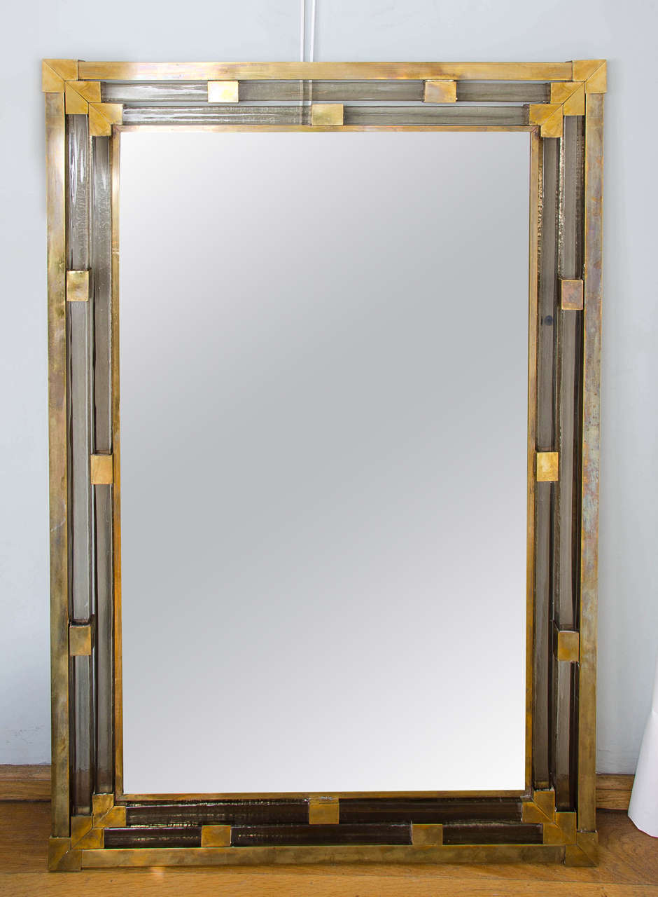 Mirror encased by four layers of thick brass and subtle smoky glass interspersed with solid cubes with triple brass corners. Classic with a twist.