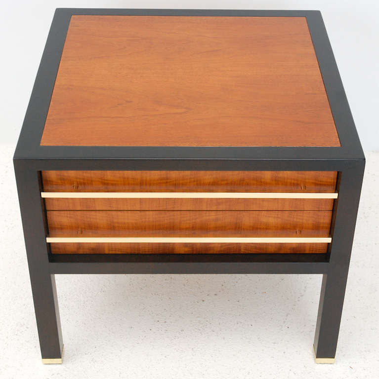 A handsome two-drawer wood side table with an ebonized frame, caned bottom shelf and brass drawer pulls and sabots. Retains the Baker emblem inside the drawer (see Image 5).