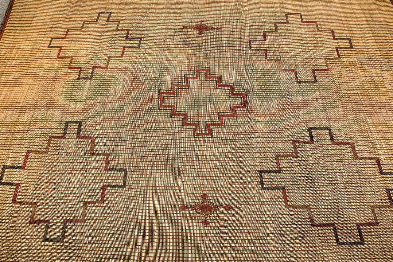Moroccan Tuareg leather mats are made of dwarf palm tree fibers and handwoven with leather stripes, this are great to use indoor or outdoor, beautiful brown earth-tone colors. This vintage Mid-Century rugs are made in the desert of Morocco near
