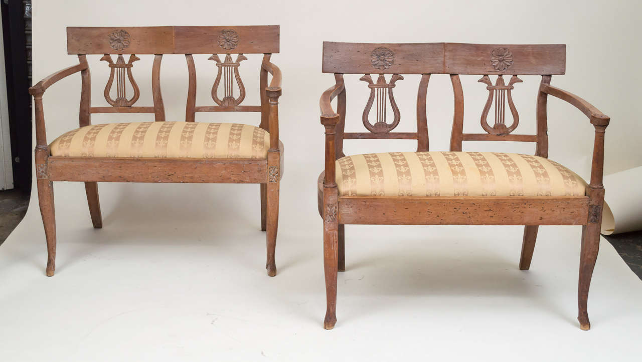 A pair of late 18th century Italian Neoclassic walnut benches. Lyre backs. Rosettes inlaid on the top backs and the legs. Hoof feet. Upholstered drop in seats with older brocade fabric. Small intimate size. Subtle lyme glazed (white) surface.