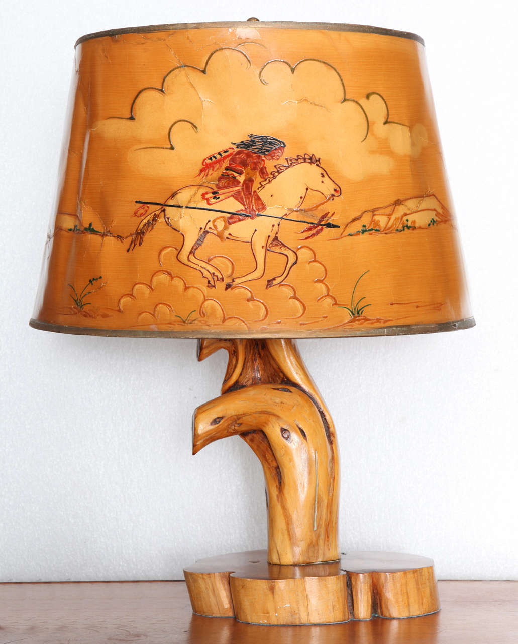 Influenced by the work of Thomas Molesworth's Shoshone furniture company, the burl root lamp base with goatskin lampshade has exquisite hand-painted scene of Indian brave on horseback hunting buffalo with spear.  Comes from Wyoming.