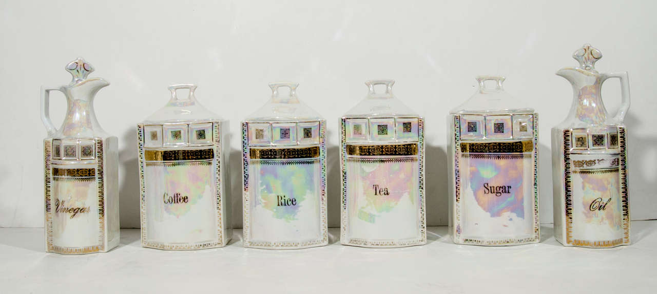 Handmade antique porcelain apothecary and spice canister set of twelve.  Have gilt details and iridescent metallic glaze or lusterware. The set includes four large canisters with lids (measuring 8.5 H x 4.5 D), six spice jars with lids (measuring 5