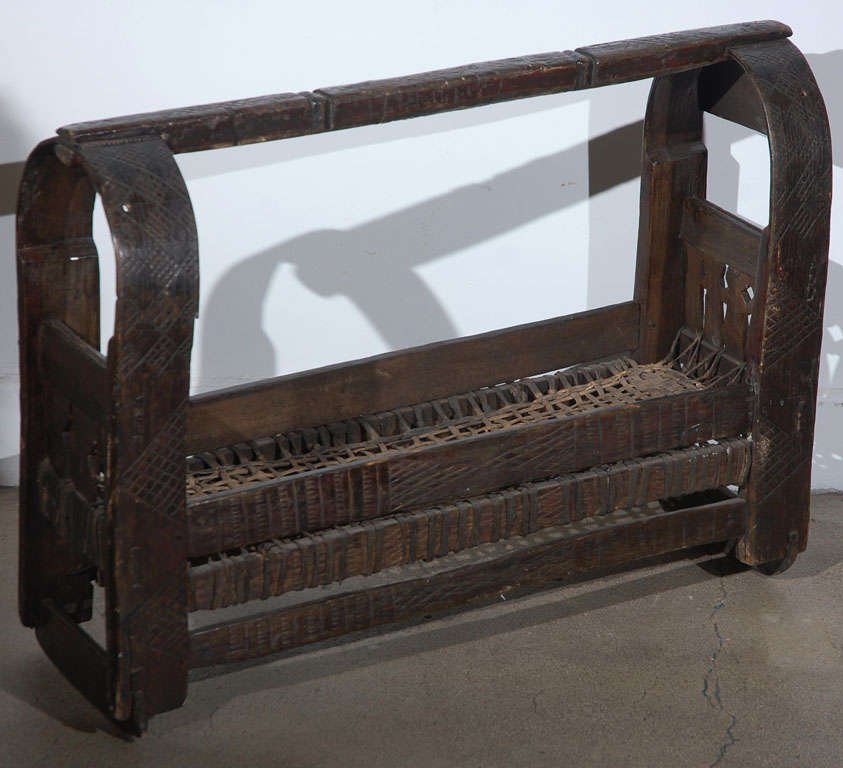 Antique African wooden storage crate, hand-carved African Tribal motifs on wood and leather woven bottom. Interested Folk Art Tribal African handcrafted crate probably Kenyan. Wooden and leather Folk Art basket. Africa, Kenya Circa 1900