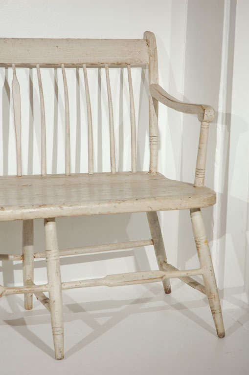 THIS FANTASTIC ORIGINAL WHITE PAINTED NEW ENGLAND SETTLE HAS REGULAR SPINDLES AND EVERY SIX SPINDLE IS ARROW BACK FORM.THE BENCH HAS MORTISSED ARMS AND WOOD PEG & SQUARE NAIL CONSTRUCTION.THE SURFACE OF THE OYSTER WHITE PAINT IS WONDERFUL.THE PIECE