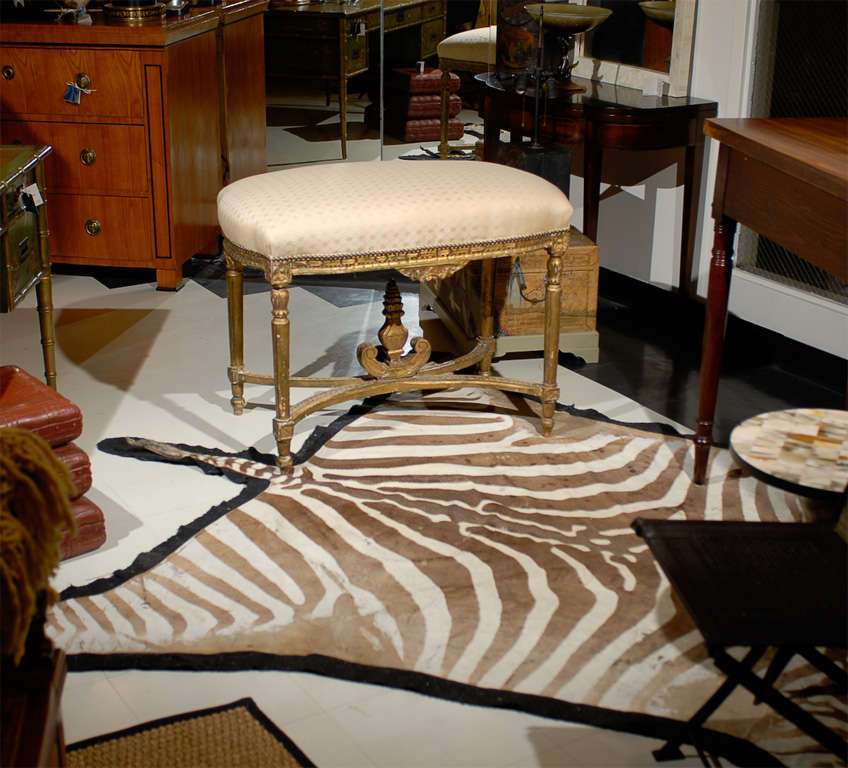 French Louis XVI style gilded stool with a carved apron and swag and rosettes carved on each corner over tapered legs. An X-stretcher supports an urn shaped ornament in the center. Custom upholstered in a cream fabric with nailhead trim.