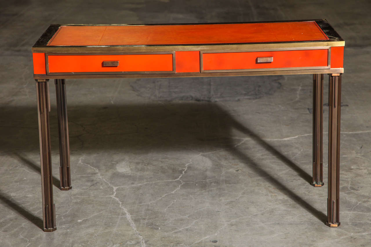 An exceptional bronze desk with orange lacquered frieze and hand-tooled leather top, circa 1960.
