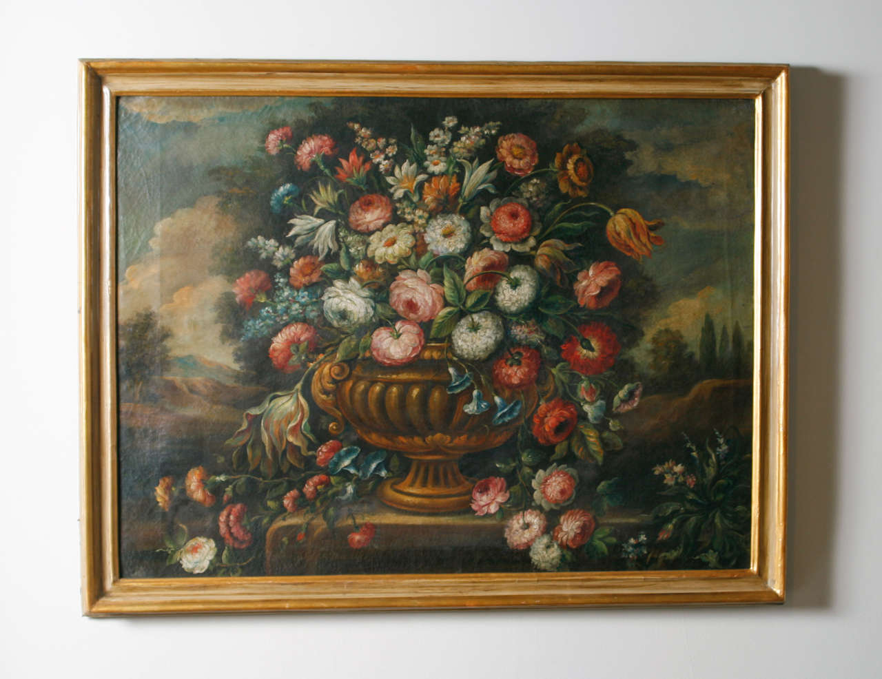Still life depicting urn with flowers within landscape.  Oil on canvas.  Later painted frame.