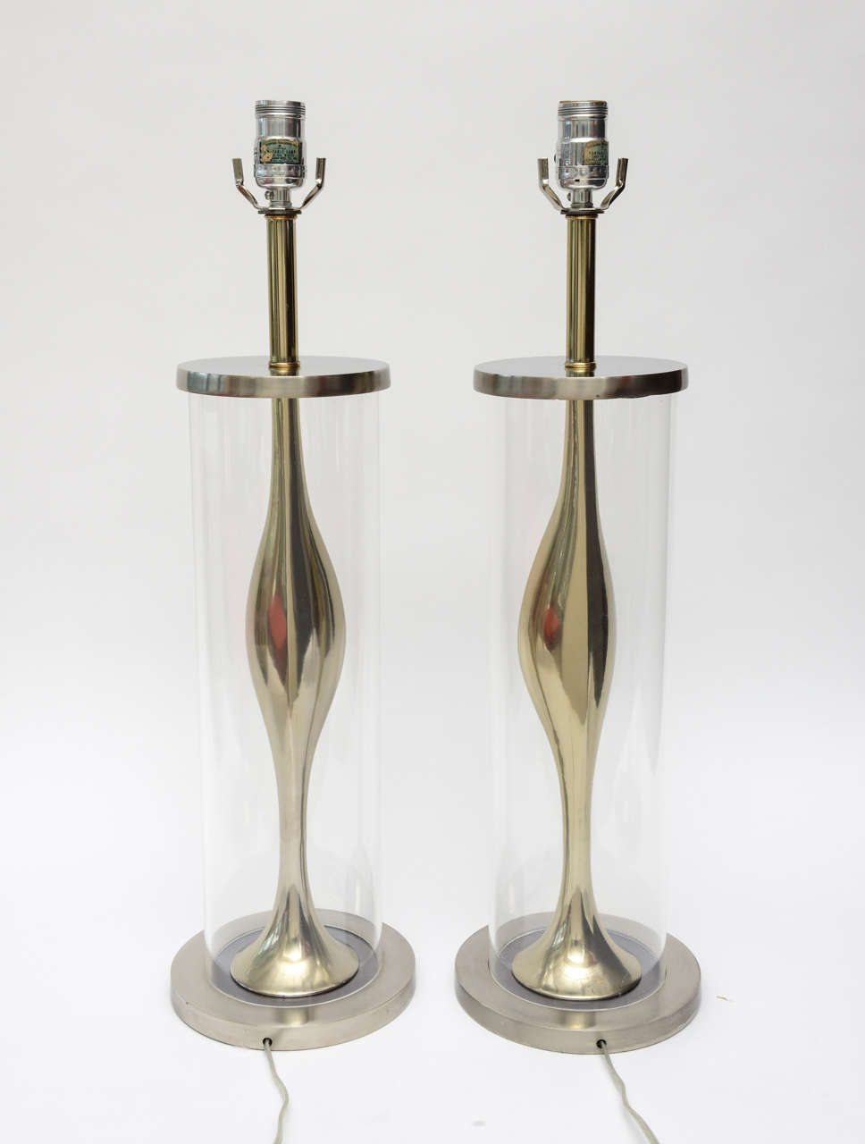 These very sculptural pair of Mid-Century Modern Laurel lamps are unusual, they have brushed stainless and polished brass with a Lucite cylinder on the outside encasing the metal work. They have a sensuality to them in their form. Laurel Lamp Co.