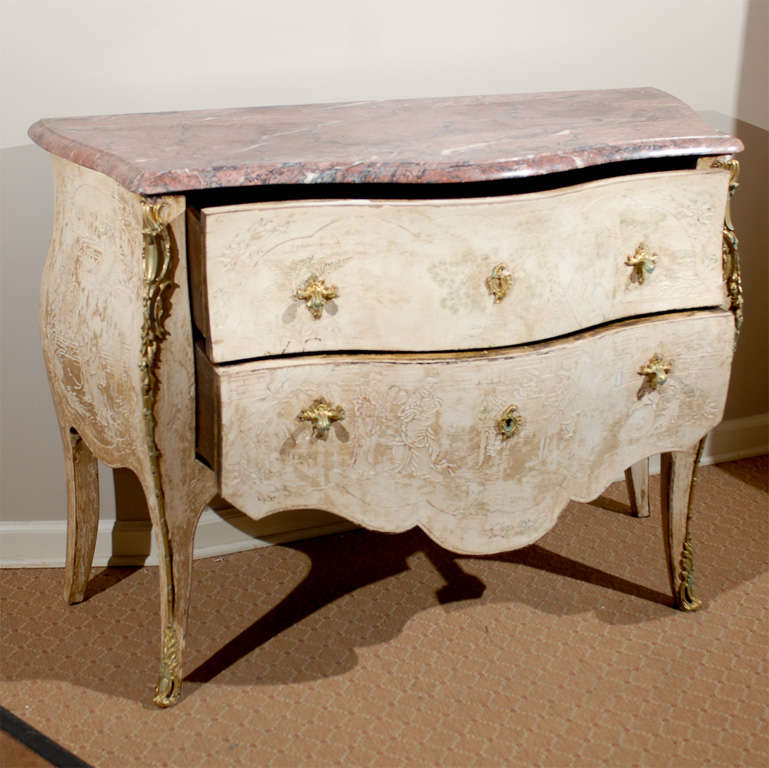 This is a beautiful, Louis XV style commode. The marble top is dominantly rosy with veined black and white running through it. The marble top is serpentine in shape, following the shape of the commode with an OG edge. It has shallow carvings of