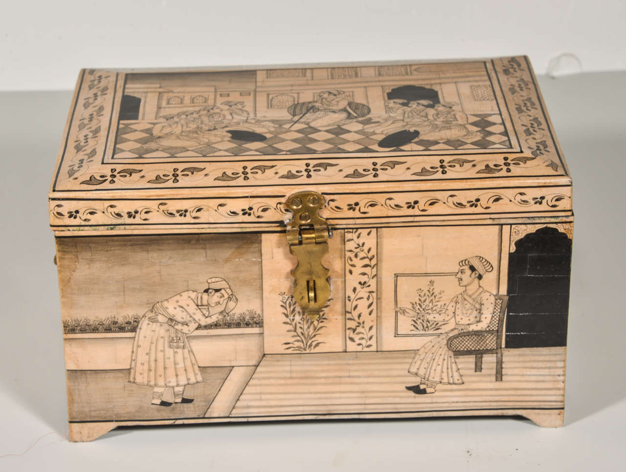 Box of camel bone veneer, incised decoration in black.  Brass handles on the side with a hinged lid.  Uttar Pradesh region of India.  Inner compartment tray with storage beneath and secret drawers on the side.