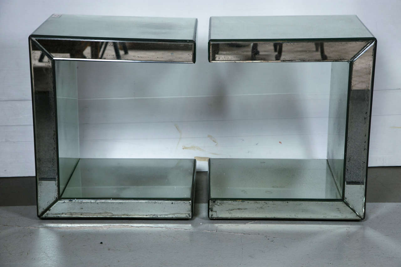 A pair of Hollywood Regency style C-shaped mirrored end tables. A pair of antiqued mirrored C-form end tables or nightstands. Each having all-over beveled antiqued mirrored glass. Both on casters for simple movement. Price is for one pair there are