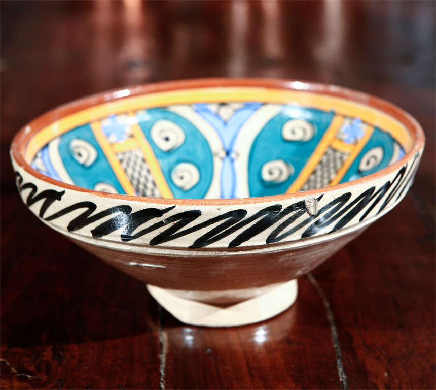 An under-glazed painted pottery bowl with abstract naive design, blue, ochre and brown.