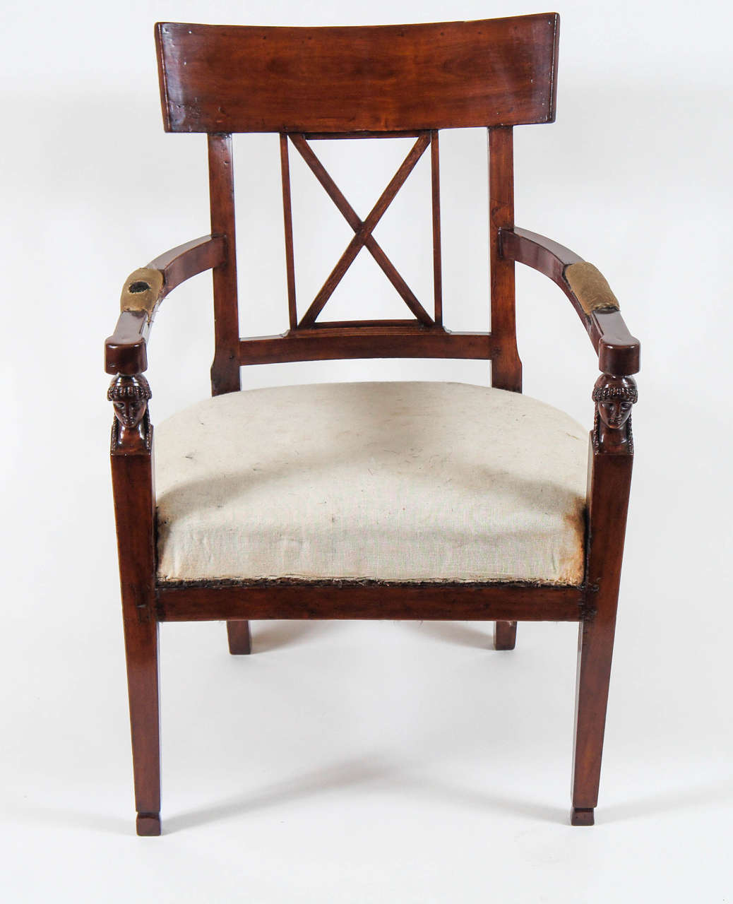 Elegant Italian, French Consulate style and period carved walnut fauteuil having Klismos style tablet form backrest above central X-form open splat, arms with padded rests terminating atop female bust term form front supports with gently splayed