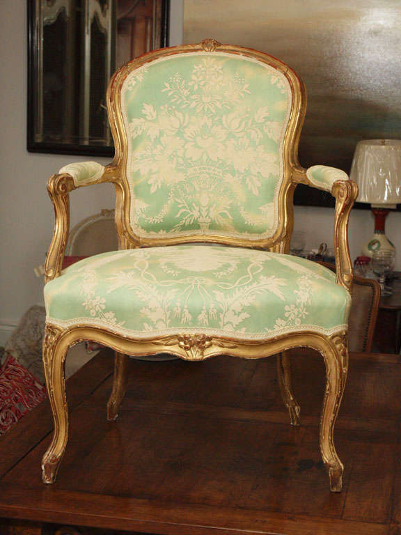 Gilt wood Louis XV Fauteuil newly upholstered in vintage Fortuny fabric.  Fortuny fabric is in green and off white.