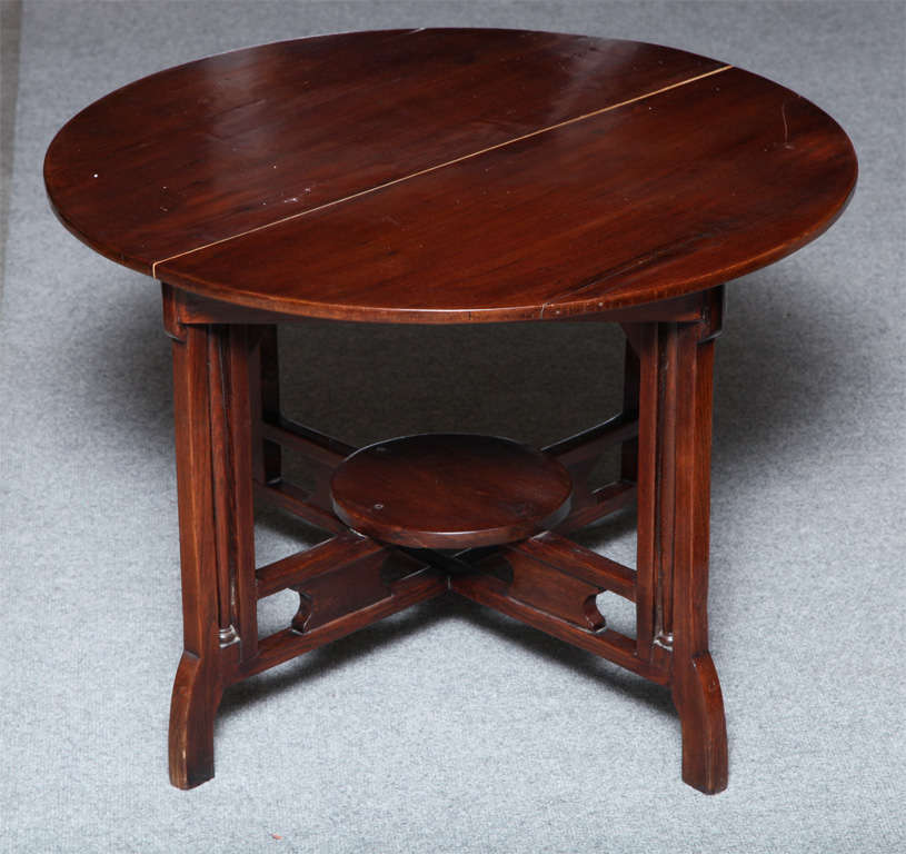 This unusual round coffee table is made of varnished elm and was carved in Shanghai in an uncommon Art Deco style. The circular top is made of two elm planks and varnished with a warm red lacquer. The table is raised on four legs with delicate