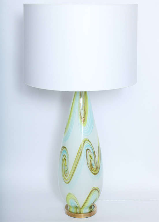 An Italian, sculptural form table lamp, produced circa 1950s, crafted of Murano art glass by Fratelli Toso, decorated with green and blue swirls, with patinated brass mounts. Shade not included