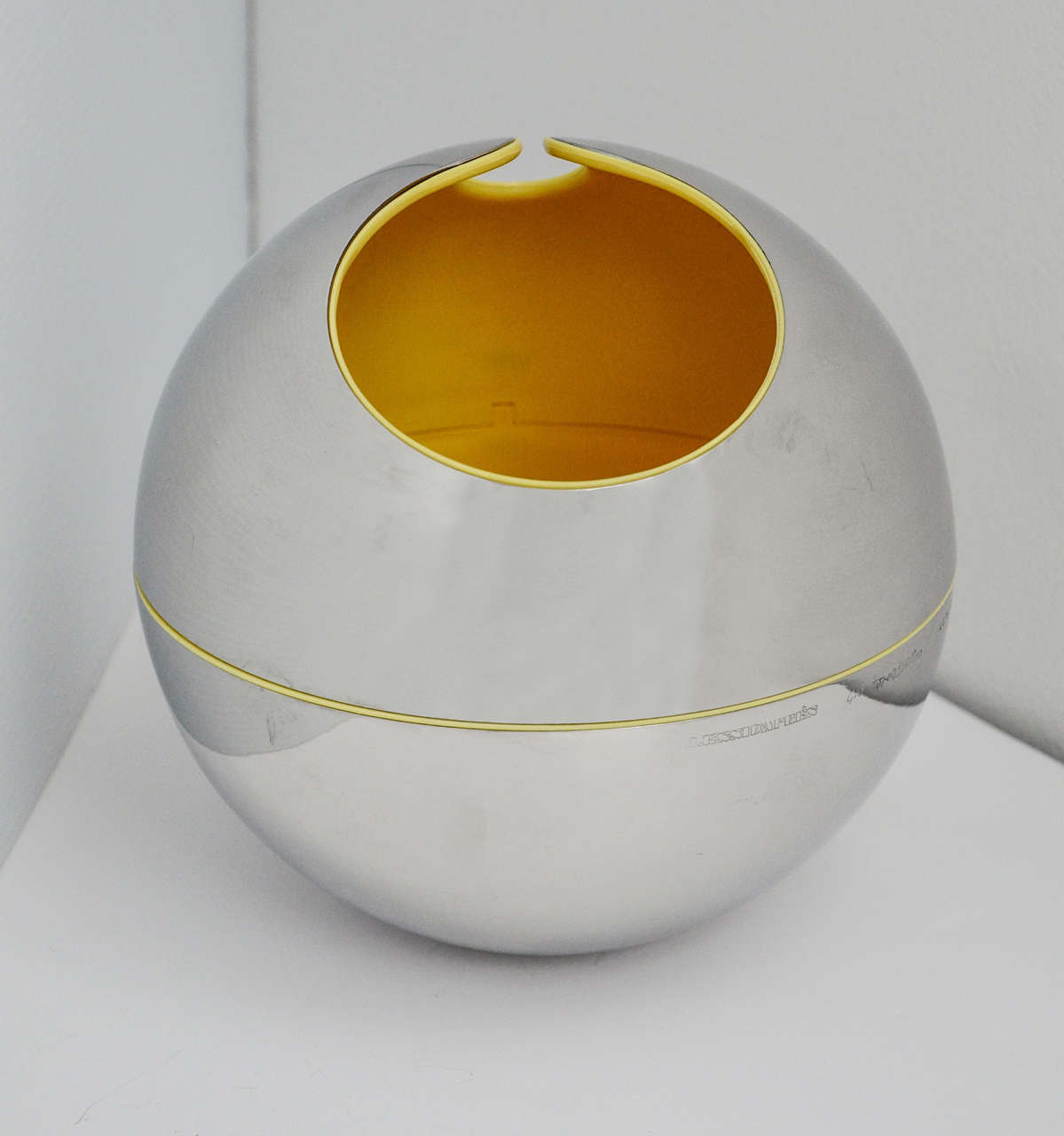 A stainless steel sphere with a yellow plastic interior designed by Gio Pomodoro for Alessi in 1972. Along with his brother Arnaldo