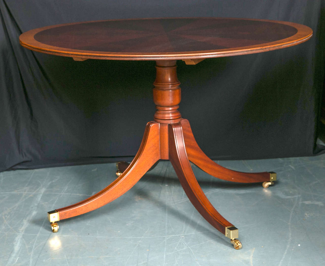 Created in the style of tables from the 18th century, this circular, mahogany starburst table is supported by a single column pedestal with four splay legs ending in brass toe caps and casters. Banded in satinwood and having a reeded edge, this