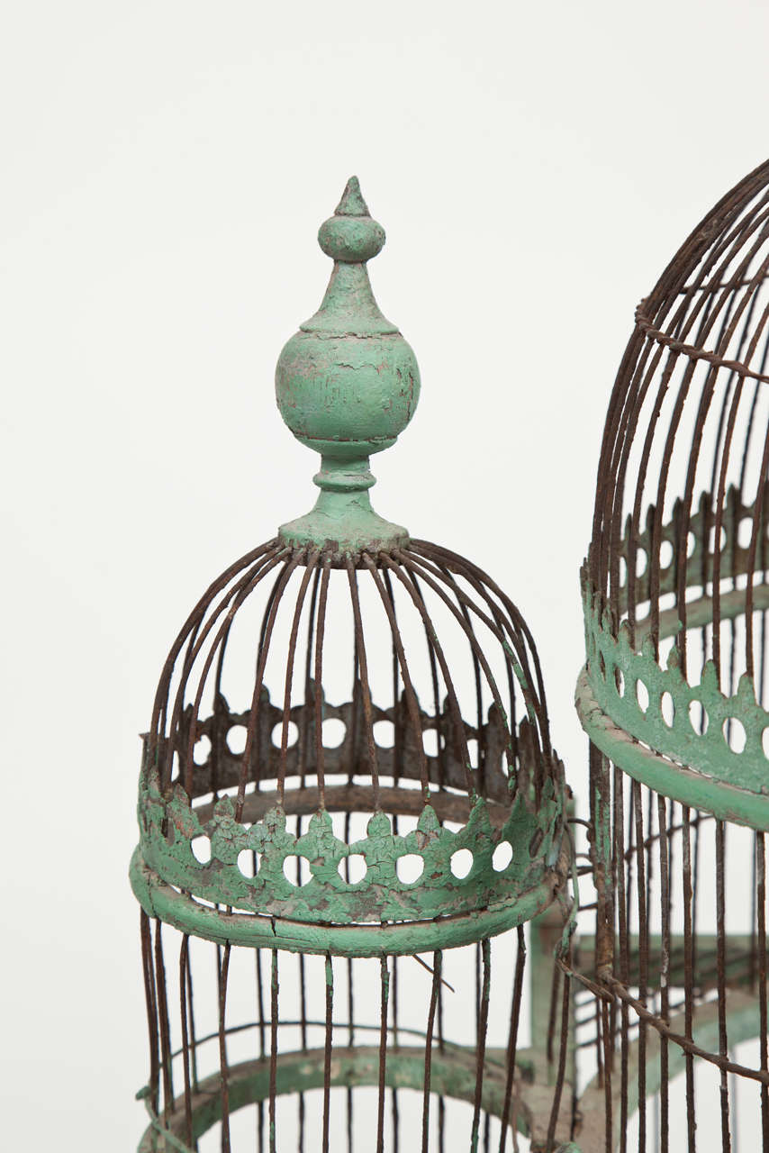 A double-domed large green painted bird-cage with side domes and onion-shaped finials. The arched doors in the main section withfleur-de-lis and with sliding trays below, and feed trays at the sides. Supported on turned feet.  Probably French,
