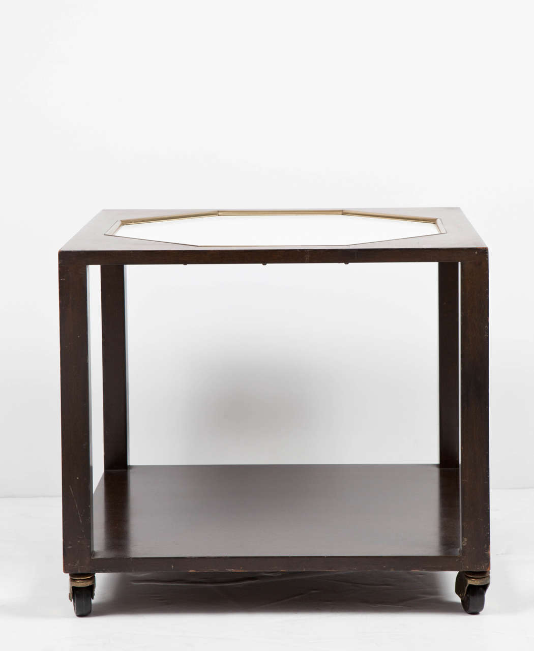 Walnut square-shaped end table with lower shelf, possibly by Harvey Probber. USA, circa 1960. Unsigned. Features a chocolate brown finish with white octagonal inset top with brass trim, complemented by removable casters.