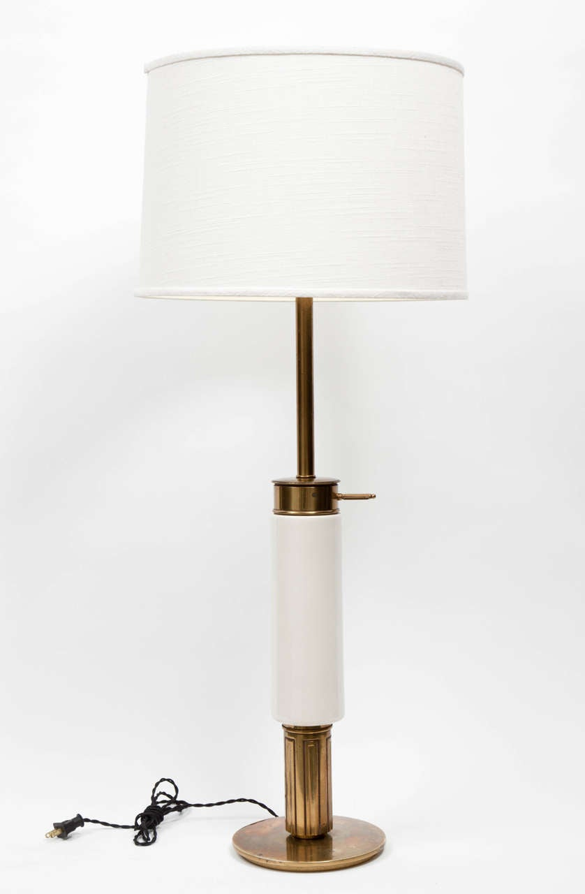Modernist white porcelain and polished brass table lamp by Stiffel, USA, circa 1950. Features cylindrical porcelain body with circular brass base. Includes white linen drum shade.