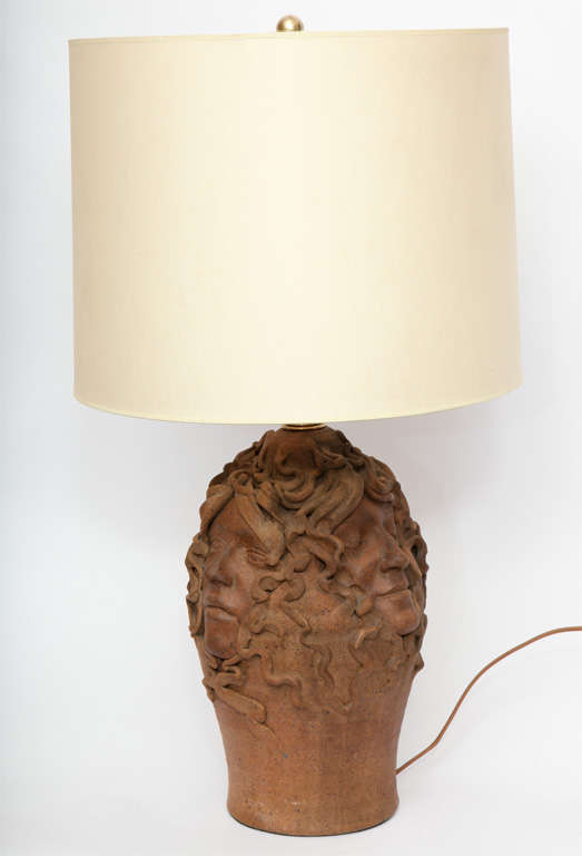 The sculptural form crafted of ceramic with woman's faces in relief. Shade not included