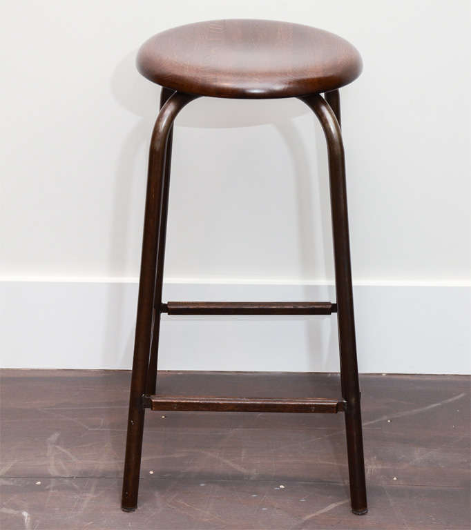 Each stool is handcrafted and made locally in the New York. Steel frame with dark bronze patinated finish, hand-carved oak seat and foot rests. Lead time is 8-10 weeks if not in stock. Available in dark or light finish. Standard size is for counter