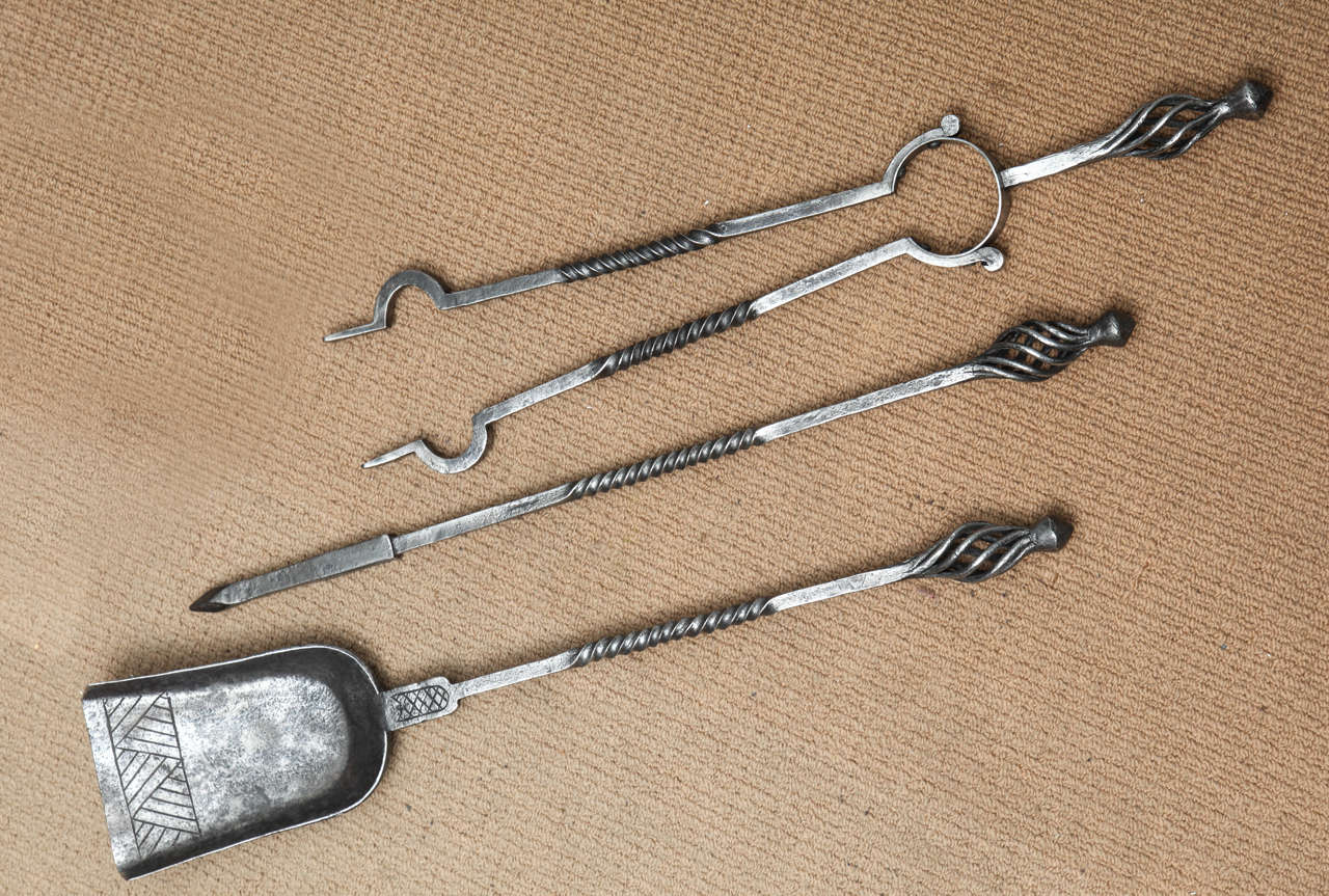 Set of three English Arts and Crafts steel fire tools, the handles with open spirals over square shafts having barley twist cnters, the solid shovel with etched decoration.