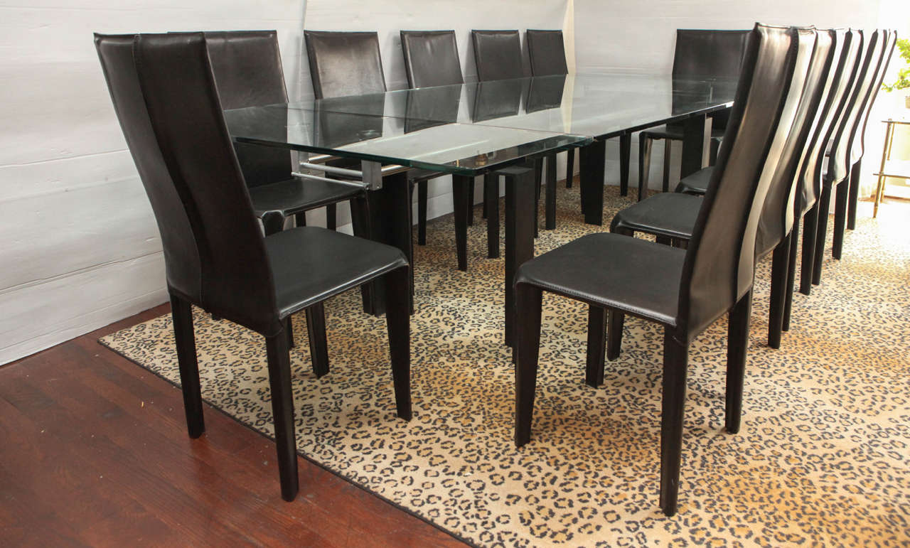 This beautiful Italian dining table set is made up of 12 leather dining table chairs, and with a beautiful large glass top dining table with black and brass steel details for dining table. Black leather Italian chairs all with markings