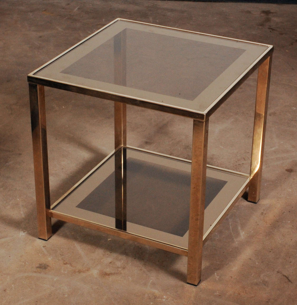 Beautiful very chic 23-carat gold (marked on a tag at the inside of the frame) coffee table consisting of a lower and upper top with the original slightly darkened and gold-bordered glass tops. There are several sizes of the identical table