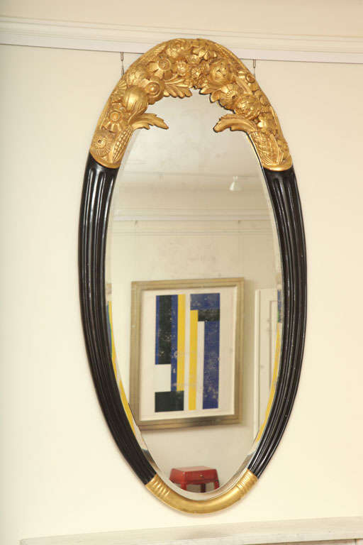 This large oval mirror by Sue (Louis Sue 1875-1968) et Mare (Andre Mare 1887-1932) has a beautiful elaborately hand-carved frame of gilt-wood on upper & lower sections. Upper section includes gilded floral carvings that extend to fluted black