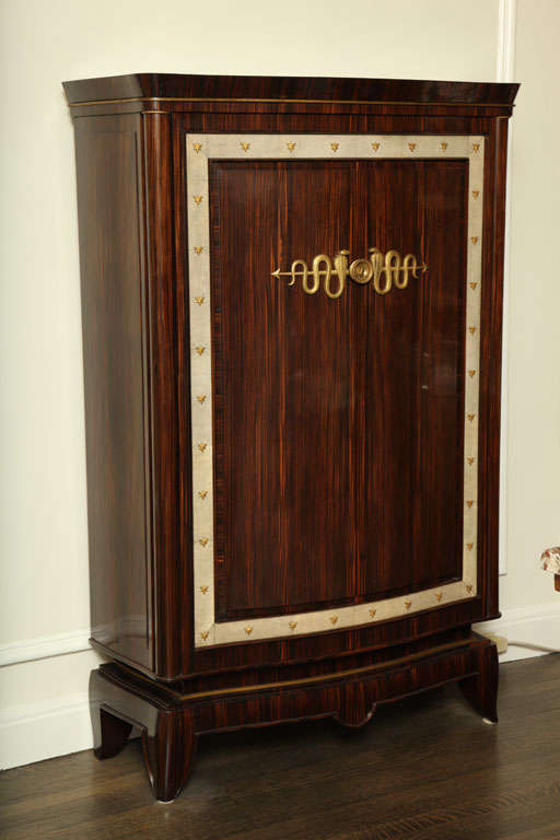 This macassar ebony cabinet has two doors which are surrounded by a strip of white shagreen and decorated with gilt bronze ornaments.   Frechet was director of the Ecoule Boulle in Paris. He participated from 1921-1935 at the Salon des Artistes