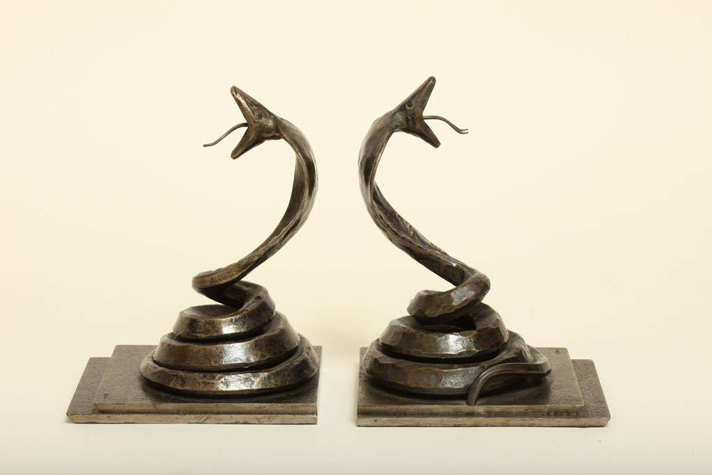Fine wrought iron cobra bookends on a stepped rectangular base with a rich dark brown patina by Edgar Brandt (1875-1968).