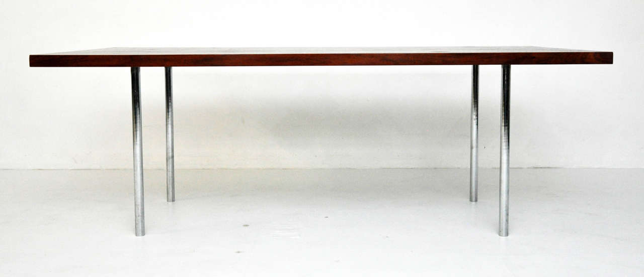 Beautiful rosewood dining table with solid stainless steel legs, circa 1960s.