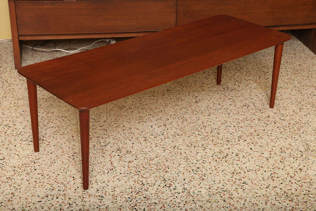 Exceptional long size and attention to detail in design features and construction sets this Danish teak table apart. First, the solid one inch thick staved teak top in a longboard length with its warm patina and beautifully figured grain. The table