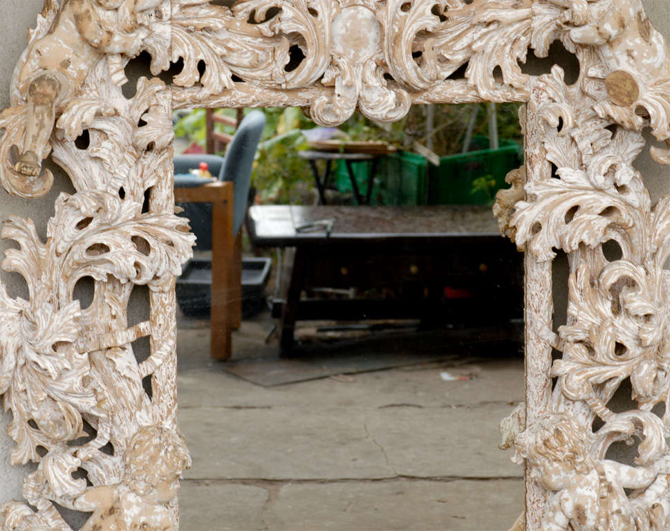 An exuberantly carved mirror with figures. Replaced glass.