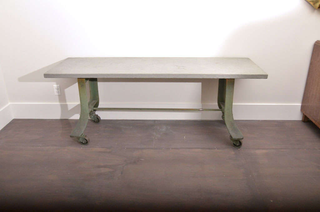 Vintage green metal table base with casters, bluestone top.