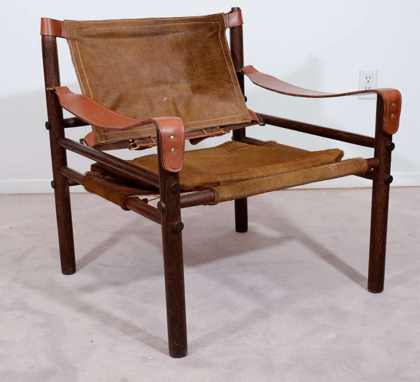 A single wood frame safari style Sirocco chair by Arne Norell. The piece has leather arm rests and furry animal hide seat and back.