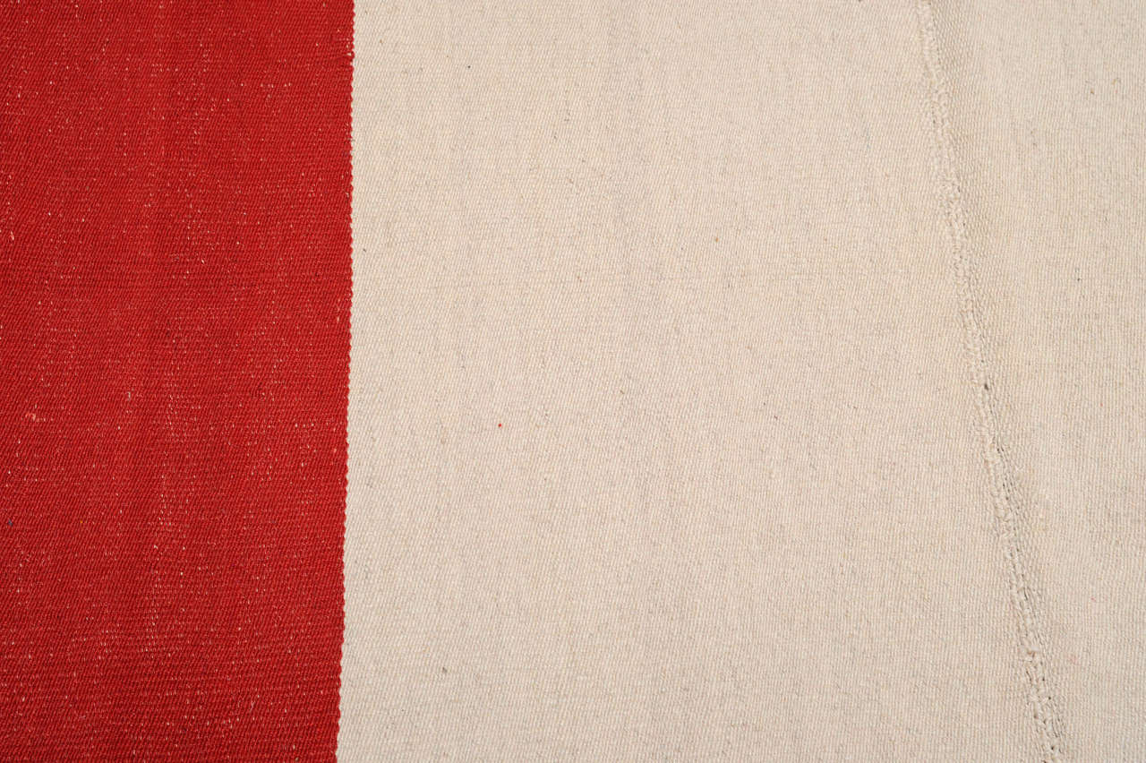 A stunning two-color wool flat-weave ascribed to the Kurds located in the Bijar area, in northwest Persia. Here a plain, undyed wool central panel is flanked by two rich red side panels. With its apparent simplicity this should be considered as a