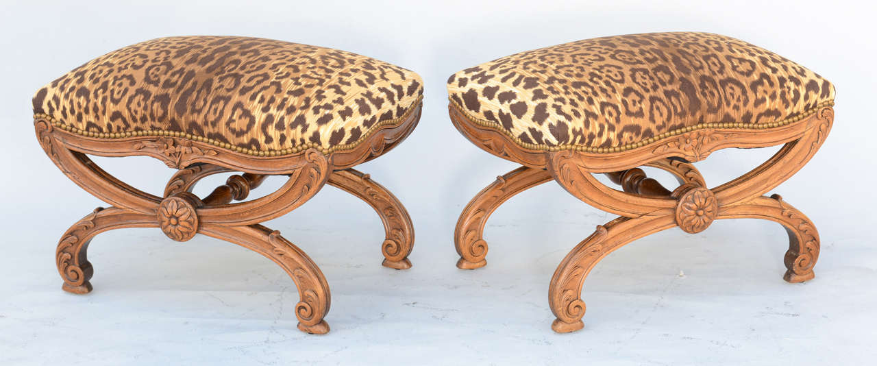 Pair of benches, or ottomans, each having a stuff-over seat upholstered with nailheads, on channeled X-frame base, its serpentine seatrail carved with flowers, raised on X-form legs carved with acanthus and scrollwork, joined by turned stretcher,