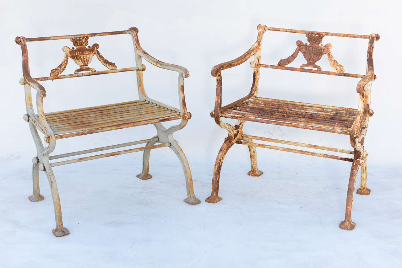 Pair of garden armchairs, of cast iron, in Neoclassical taste, each backsplat inset with floral-filled urn flanked by festooning, downswept arms raised on S-scroll terminals, its grille seat raised on X-frame legs, with double stretcher.  Stock ID: