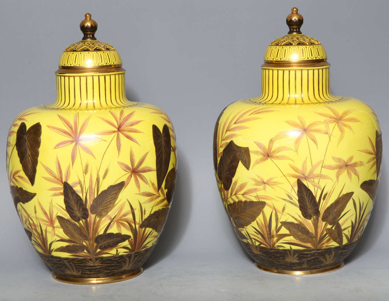 A very unusual pair of antique English Royal Crown Derby porcelain, yellow ground covered potpourri vases, finely painted with multicolored 24-karat gold and enamel. Each finely signed inside the reticulated cover in red.
