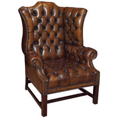 Antique English brown leather wing chair.