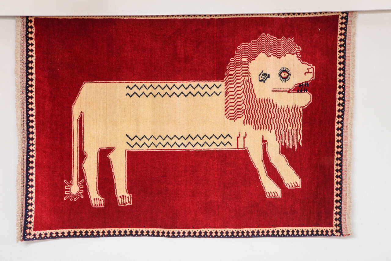 This 1940 Persian Qashqai carpet consists of a handspun wool warp, weft and pile and natural vegetable dyes. Although the color palette of rich red and natural beige is minimal compared to other Qashqai animal rugs, the effect is rather striking,