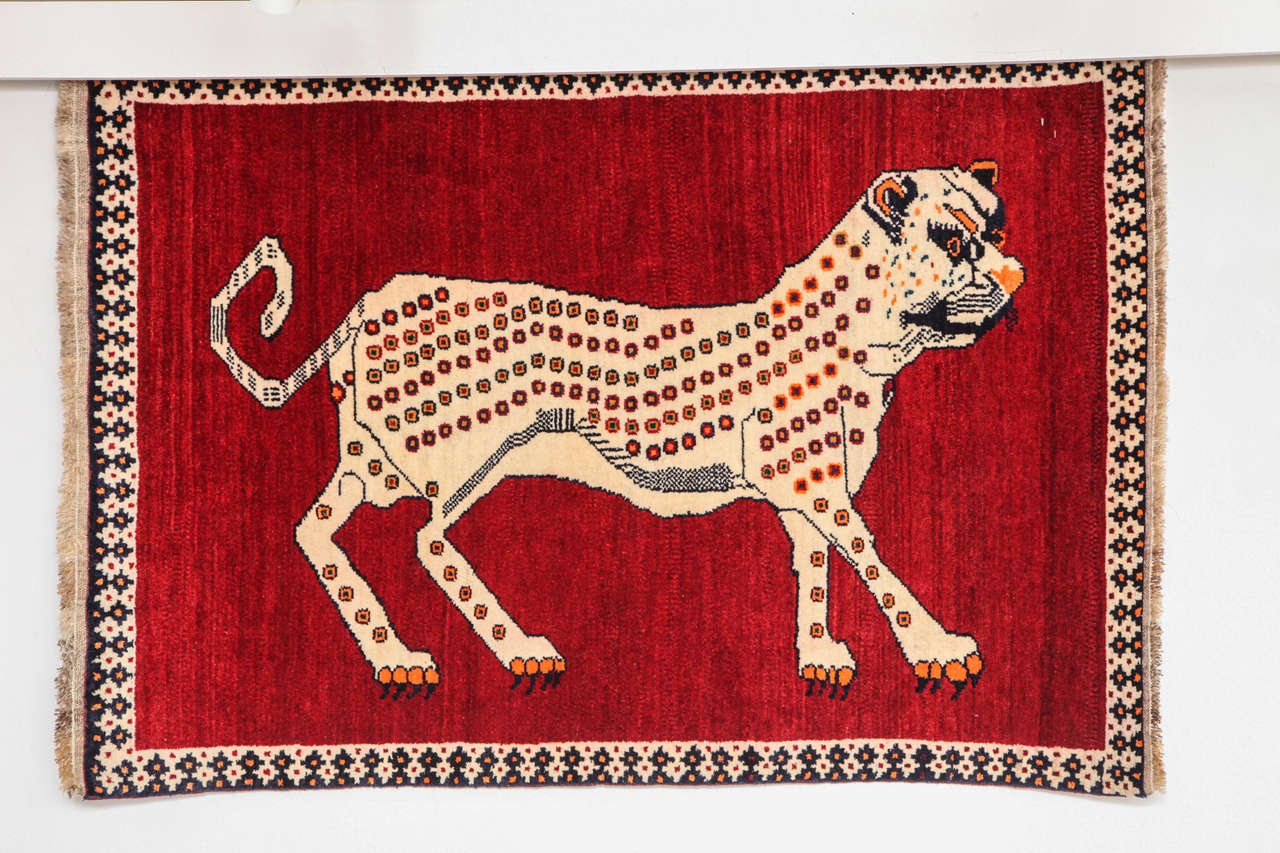 This Persian Qashqai carpet created circa 1940 consists of a handspun wool warp, weft and pile and natural vegetable dyes. The vibrant red field accentuates the striking image of the carpet's central leopard, completed in beige with black and orange