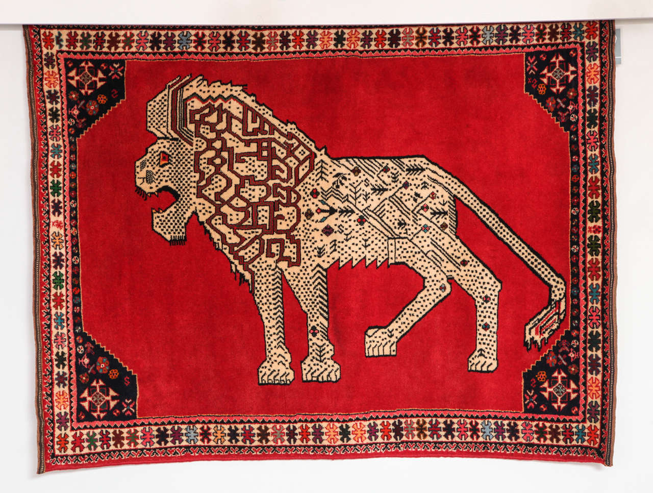 This Persian Qashqai carpet created, circa 1940 consists of a handspun wool warp, weft and hand-knotted pile and natural vegetable dyes. Its highly detailed central lion design is balanced by the carpet's strong red field and colorful geometric