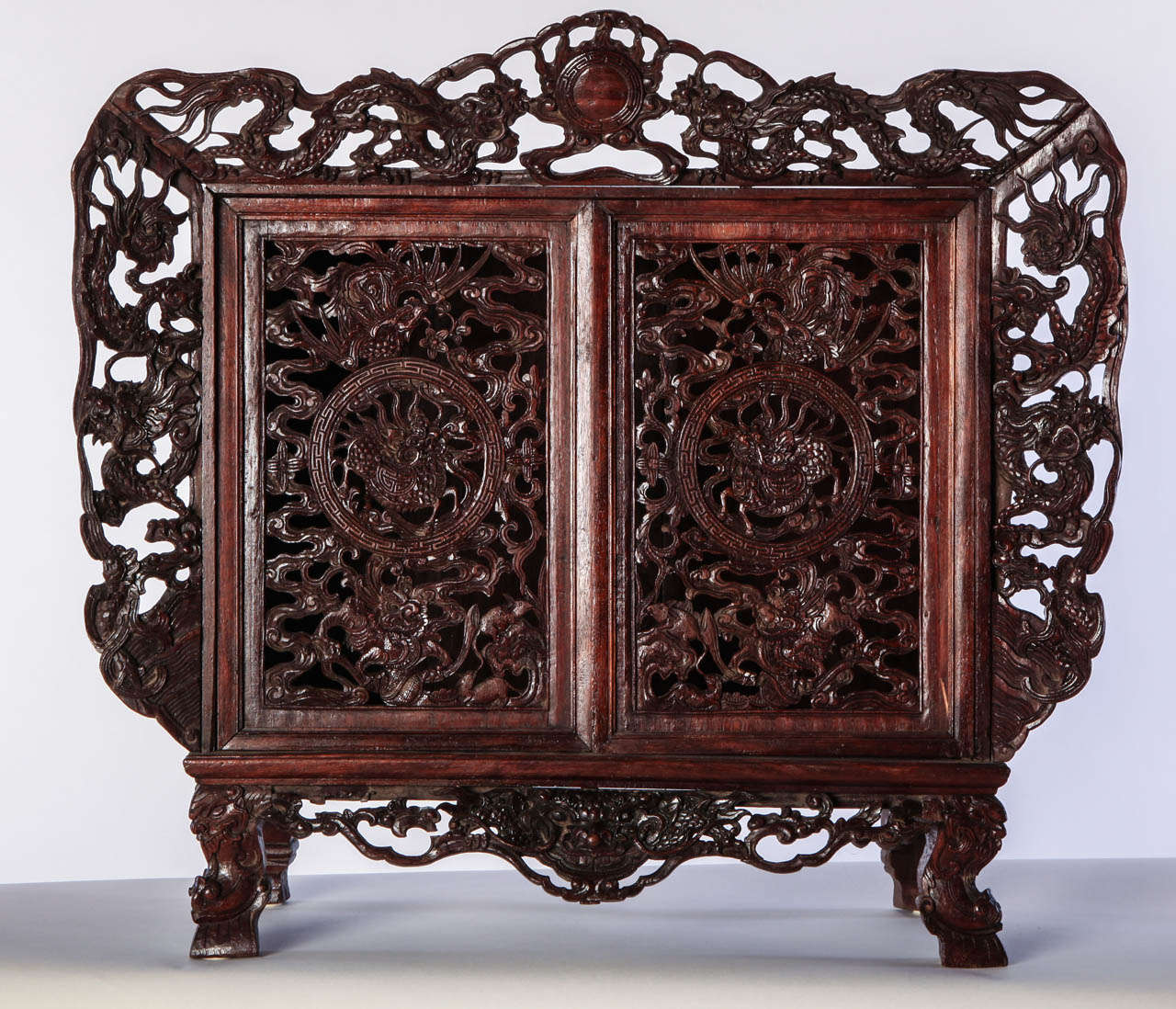 A SMALL OPENWORK WOOD CABINET DEPICTING DRAGONS, China  Size61x67x25 cm