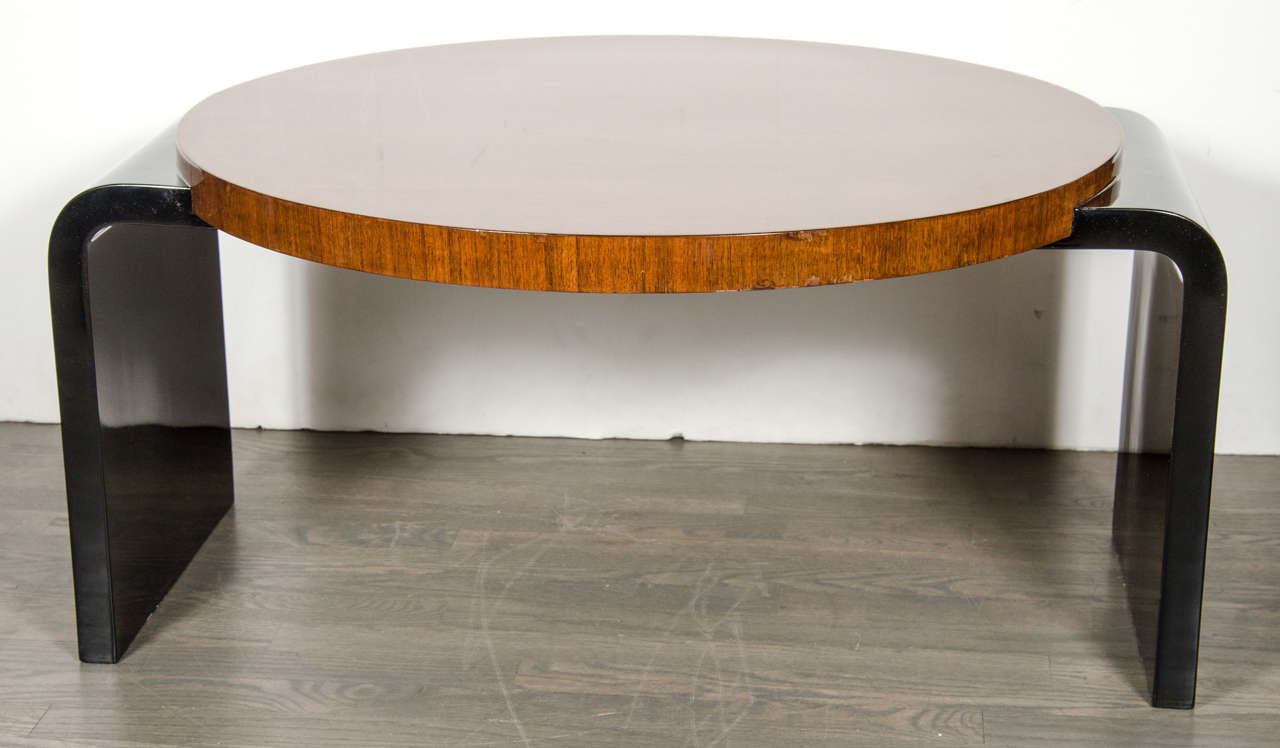 This Machine Age occasional or cocktail table was realized by the esteemed design house Modernage of New York, circa 1935. The piece features a circular book-matched walnut top with waterfall supports in radiant black lacquer. The high keyed